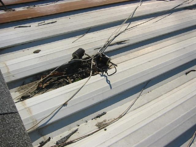 Electrical service wires laying on metal roof- Home inspection in San Diego- Shock hazard